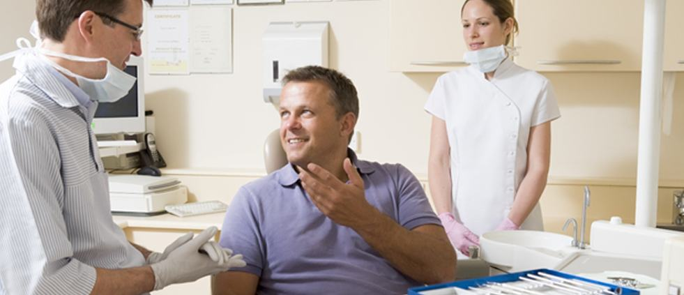 A male patient talking to his dentist