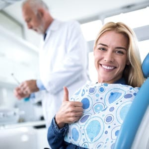 person giving a thumbs-up while sitting in a dentist's chair