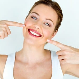 A woman pointing to her healthy smile