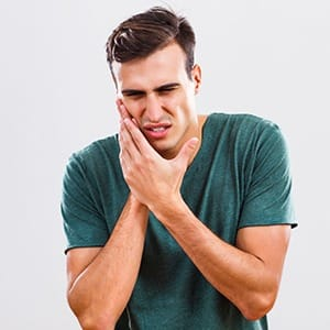 young man with toothache who needs emergency dentist in Lincoln