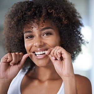 young woman smiling and flossing