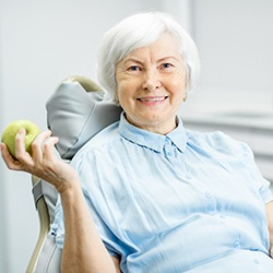 older woman admiring her smile with dental implants in Lincoln