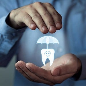 Hands holding animated tooth under umbrella