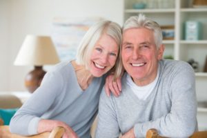 older couple smiling with dental implants in Lincoln